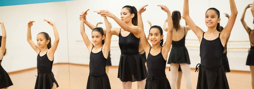 portrait of a little girl enjoying her ballet class with a group of girls and a dance teacher